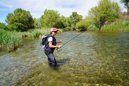 woman fishing in the river Foto de archivo - 124707749