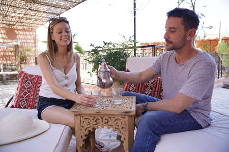 Couple at roof top of riad hotel drinking moroccan mint tea
