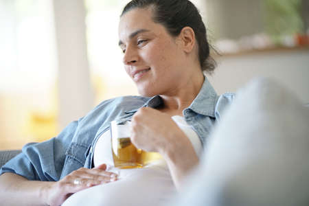 Pregnant woman relaxing in sofa drinking hot tea