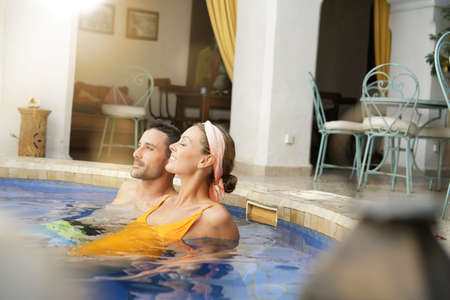 Couple relaxing in Moroccan riad swimming pool