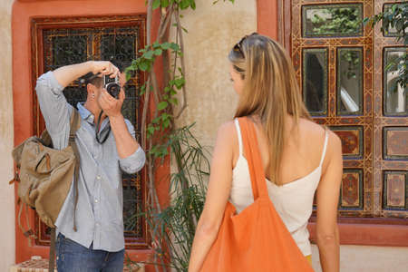 Man taking photo of girlfiend in moroccan riad