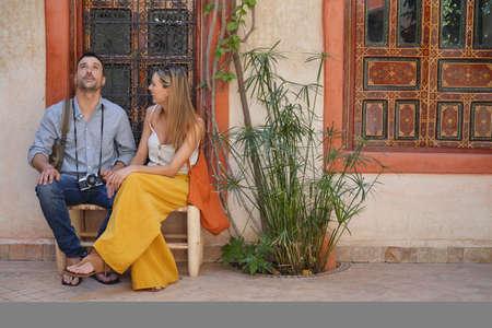 Couple sitting in beautiful Moroccan riad Banco de Imagens