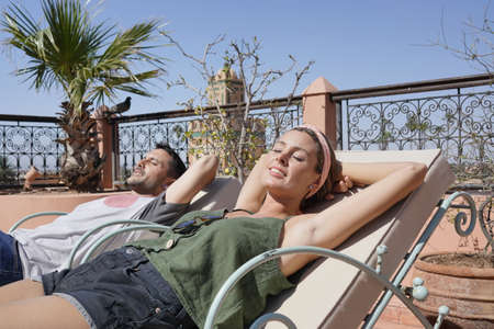 Couple sunbathing on moroccan riad rooftop Banco de Imagens