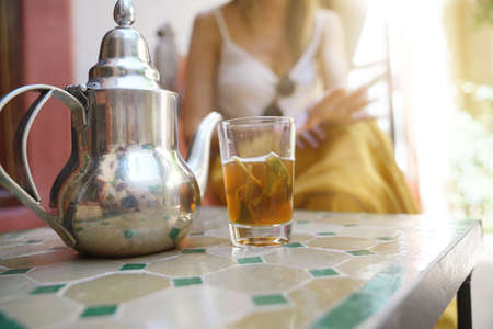 Close up of traditional Moroccan min ttea with girl in background Stockfoto