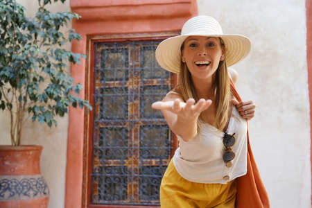 Stylish woman reaching towards camera in traditional Moroccan riad