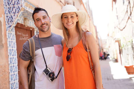 Attractive couple smiling at camera in moroccan street