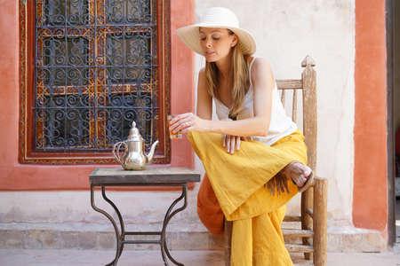 Elegant woman dirnking mint tea in Moroccan riad
