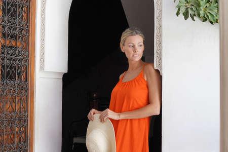 Elegant woman in bright dress standing in moroccan riad Stockfoto