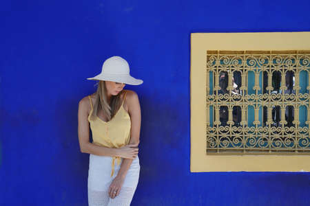 Stunning woman against blue wall in Majorelle Garden Morocco