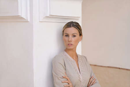 Natural beauty leaning against pillar in Moroccan villa in neutral tones Stockfoto