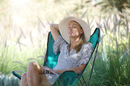 Beautiful woman resting in lawn chair in countryside