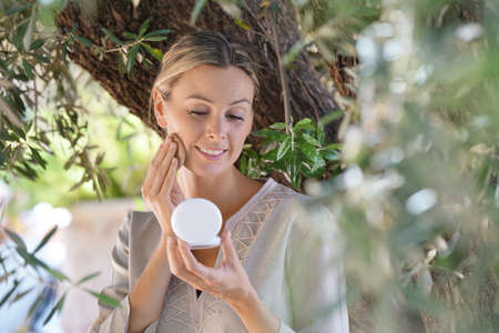 Beautiful woman applying make up outdoors
