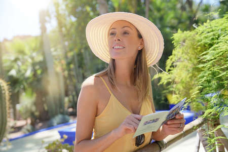 Cheerful woman looking at map in Majorelle Gardens Stockfoto