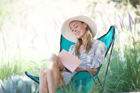 Beautiful woman writing in journal in countryside