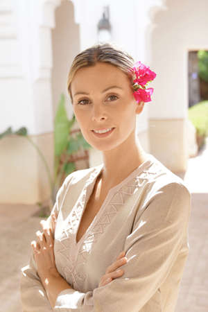 Natural beauty with flower in hair standing in Moroccan villa