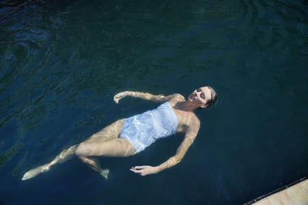 Top view of elegant woman swimming in black tiled pool Imagens