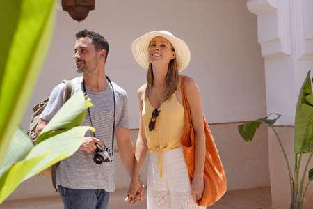 Cheerful couple exploring Moroccan villa and gardens
