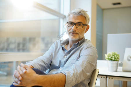 Portrait of smart casual businessman looking at camera in contemporary office