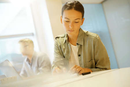 Woman working next to colleague in contemporary office