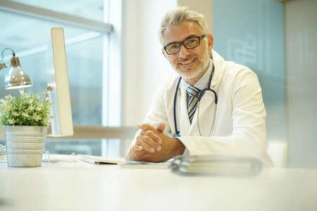 Portrait of handsome mature doctor sitting at desk in modern office Reklamní fotografie
