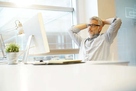 Relaxed businessman sitting at desk with arms behind head Reklamní fotografie