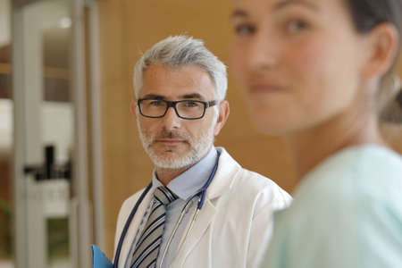 Portrait of doctor looking at camera with nurse in foreground Reklamní fotografie