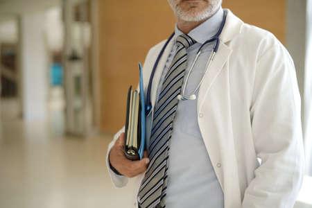 Close up of doctor holding patient files in hospital hallway Reklamní fotografie
