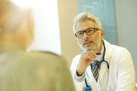 Mature doctor talking to patient in modern clinic