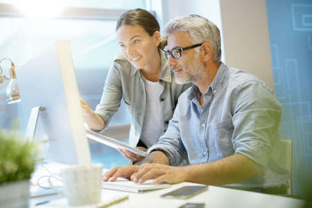 Smiling coworkers working together in contemporary office Stock Photo