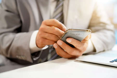 Close up of businessmans hands using stylus pen on cellphone