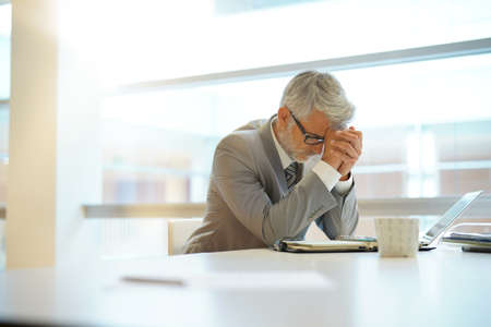 Stressed out businessman sitting at desk Stock Photo