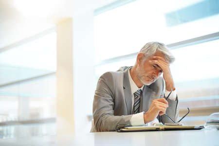 Exhausted businessman sitting at desk