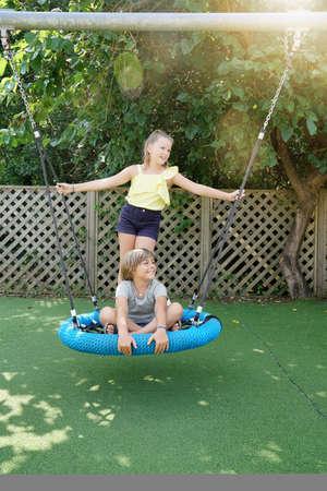 Kids playing on a swing Stock fotó