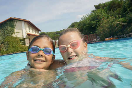 Cheerful kids with gogles at the swimming-pool