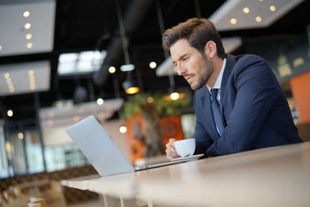 Businessman working on laptop while waiting to meet client