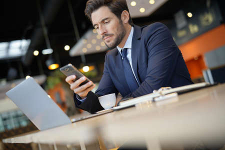 Businessman connected at the airport with smartphone