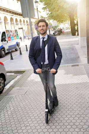 Businessman in town using electric scooter