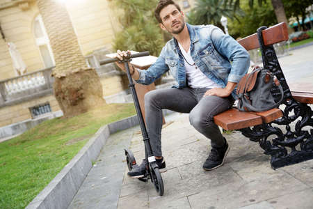Trendy guy in town using electric scooter