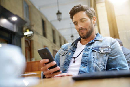 Trendy guy connected on smartphone at coffee shop Stok Fotoğraf
