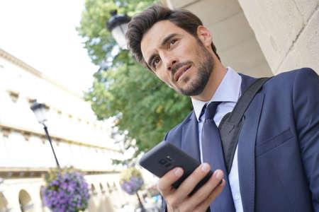 Businessman in the street using smartphone 版權商用圖片