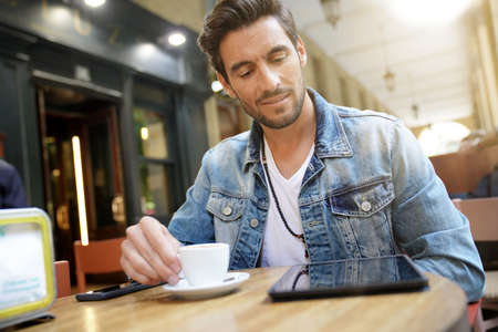 Trendy guy connected on tablet at coffee shop