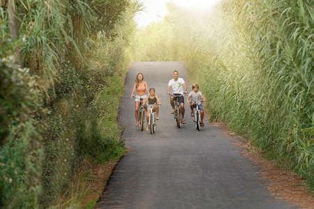 Happy family on vacation riding bikes