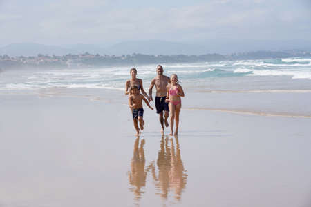 Family running on a sandy beach at low tide