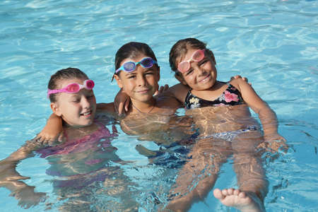 Cheerful group of kids at the swimming-pool Фото со стока