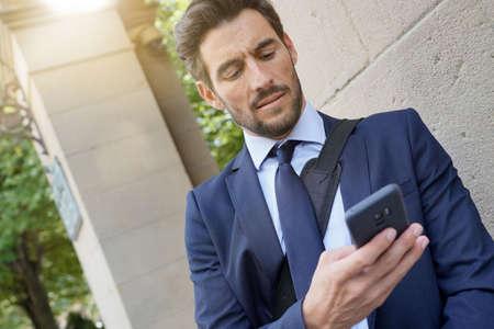 Businessman in the street using smartphone 版權商用圖片 - 129864002
