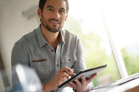 Modern man working on digital tablet in office