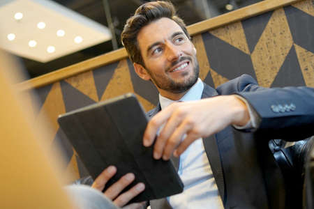 Businessman working on tablet at airport waiting room