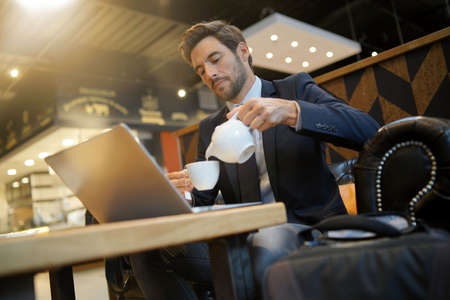 Businessman at airport coffeshop drinking hot tea 스톡 콘텐츠