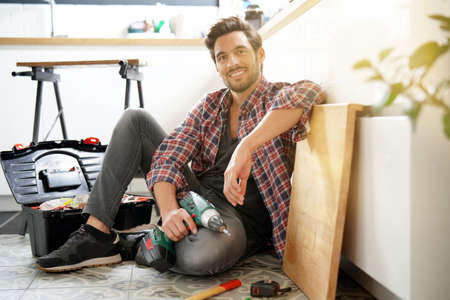 Young guy at home sitting on floor after repairing stuffs