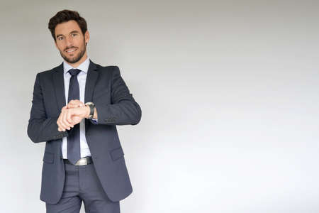 Businessman on white background, checking time